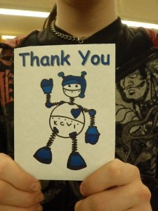 A member holding a thank you card